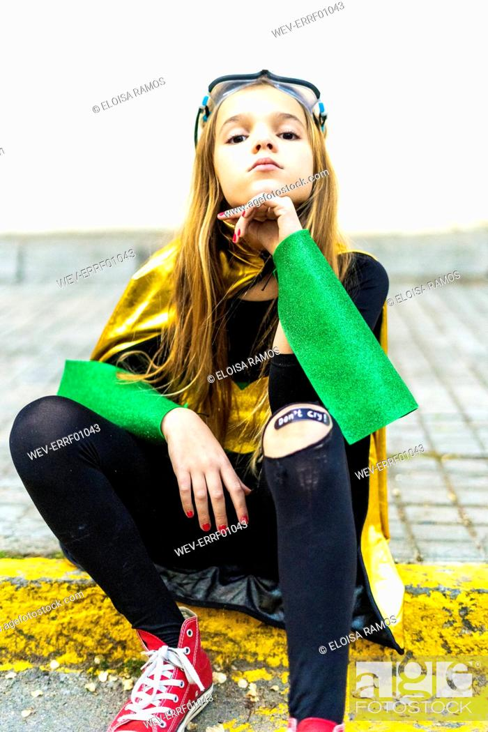 Stock Photo: Girl posing in super heroine costume sitting on curb.