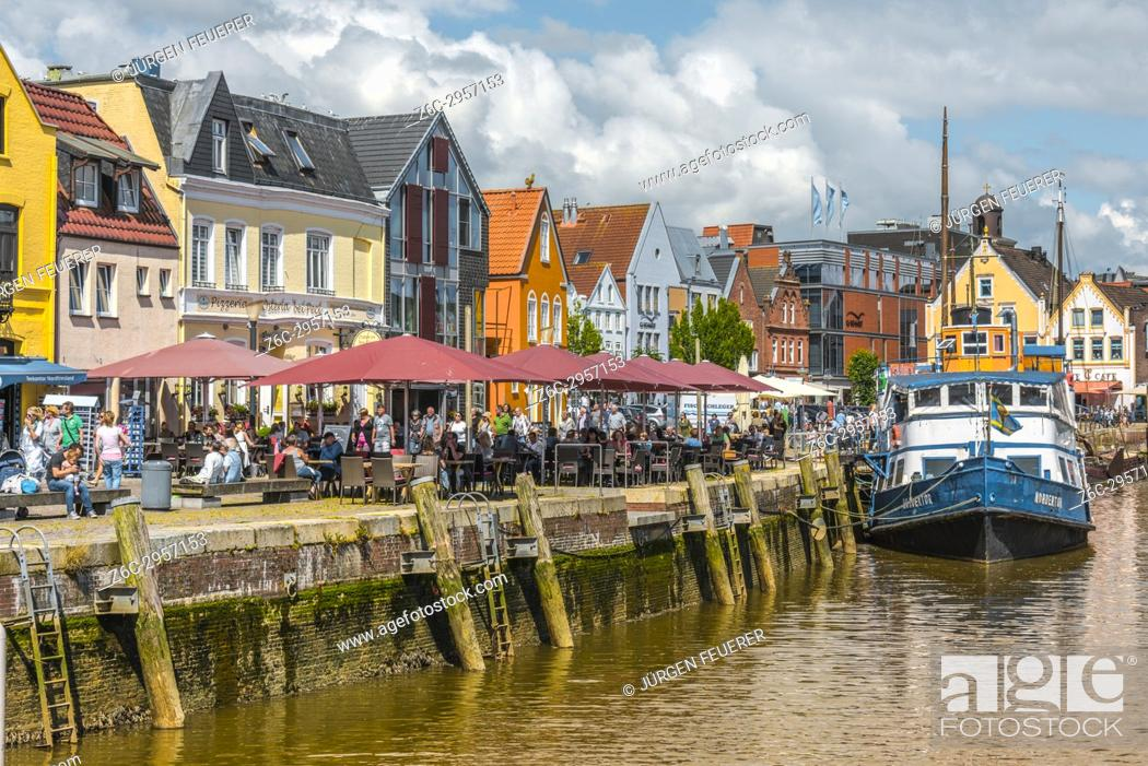 Stock Photo: pavement café and fish restaurants at the pier, inner harbour of the coastal town Husum at the North Sea, Germany.