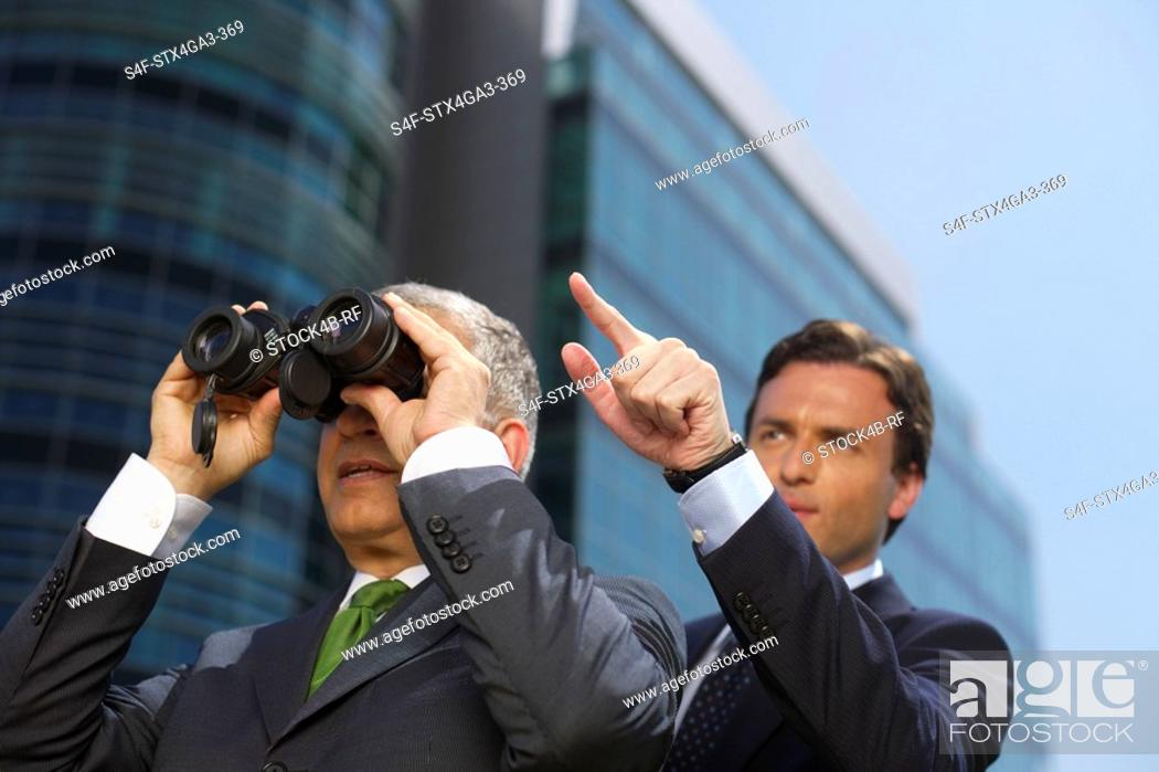 Stock Photo: A man showing something to another man with a spyglass.