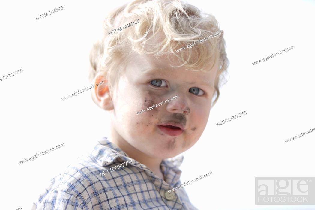 Stock Photo: Germany, Bavaria, Boy with charcoal on his face, close up.