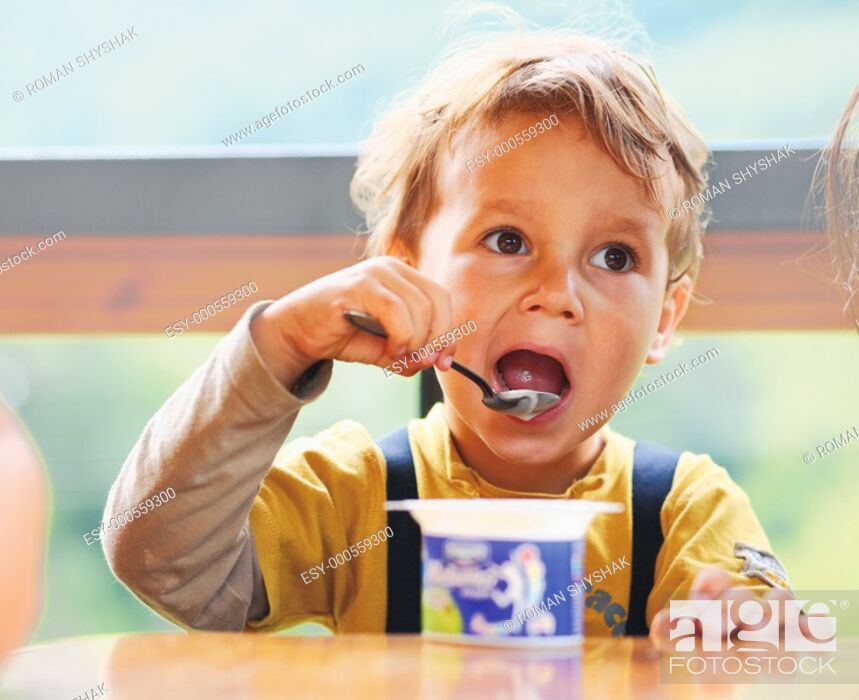 Stock Photo: Little boy is eating yogurt, holding a spoon in his hand, sitting at the table.