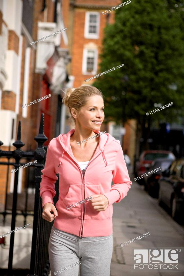Stock Photo: A mid adult woman jogging in the street.