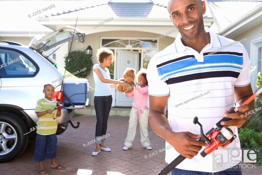 Stock Photo: Man with fishing rod in driveway, family by car in background, smiling, portrait.