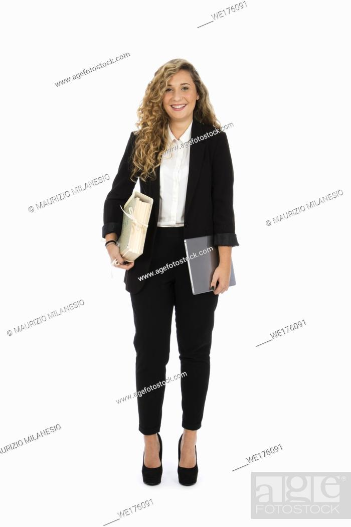 Stock Photo: Businesswoman standing in the studio with computer and documents under her arms, she is wearing a black suit and a white shirt.