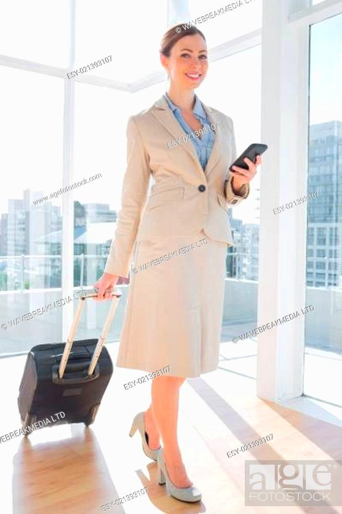 Stock Photo: Businesswoman walking with suitcase and checking her phone.