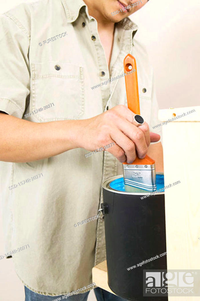 Stock Photo: Mid section view of a young man dipping a paintbrush into a paint can.