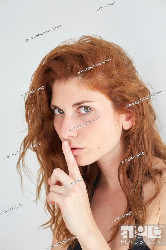 Stock Photo: Young redhead woman with finger on her lips, looking at camera.