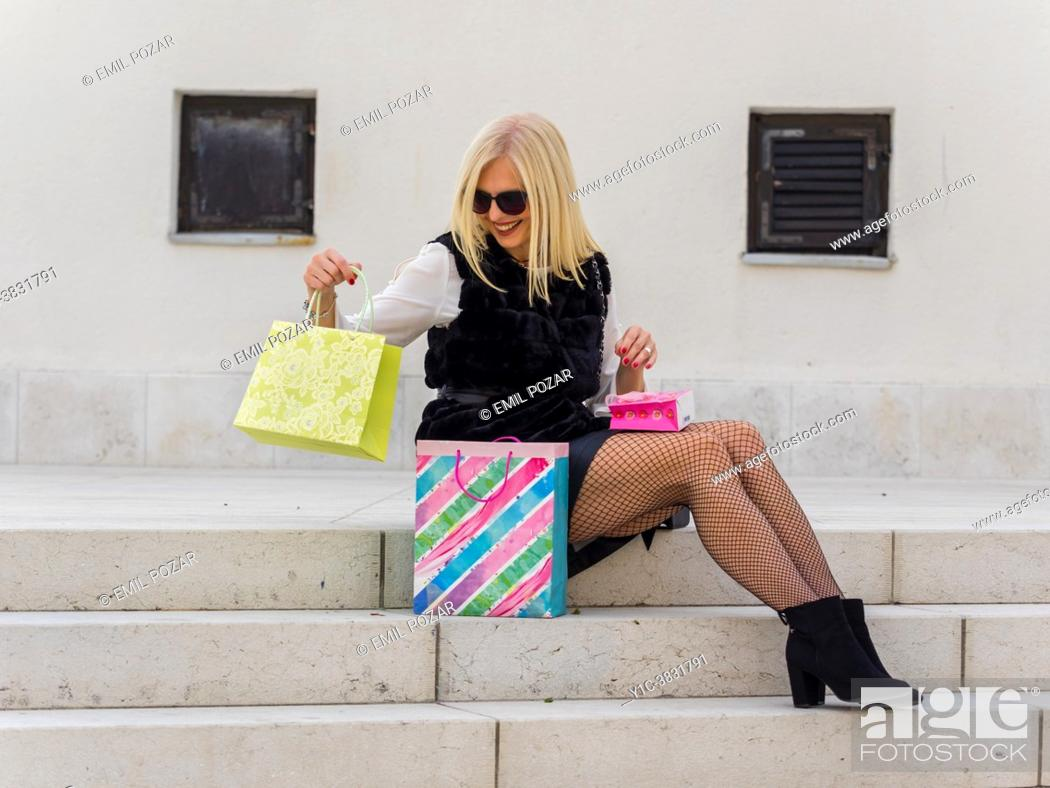 Stock Photo: Attractive mature blonde woman is checking her shopping bags, smiling.