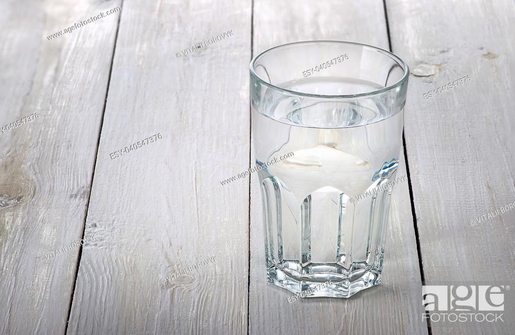 Stock Photo: A glass of water on a white wooden table. Blurred background.