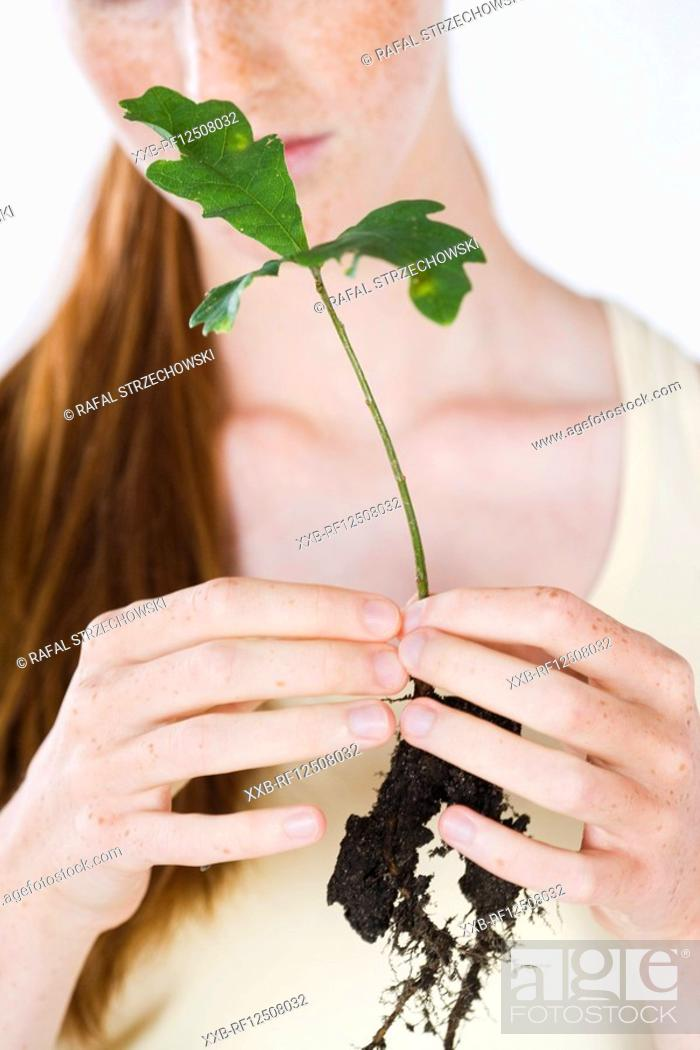 Stock Photo: young woman holding plant.