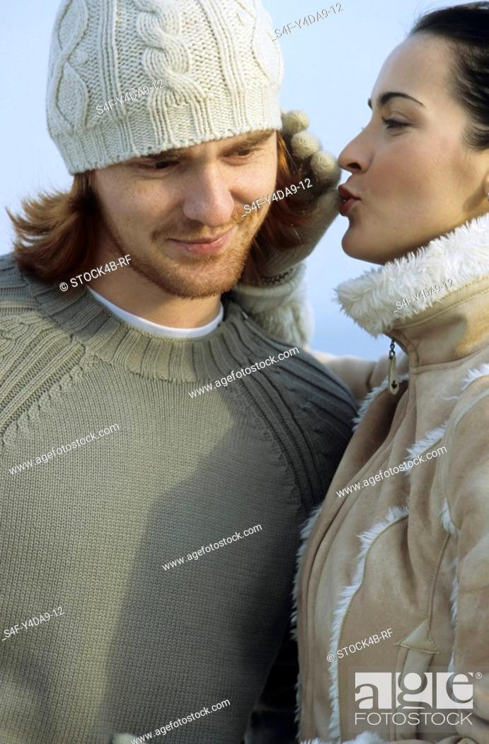 Stock Photo: Young brownhaired Woman blowing into her Boyfriend«s Ear - Fondling - Relationship - Winter.