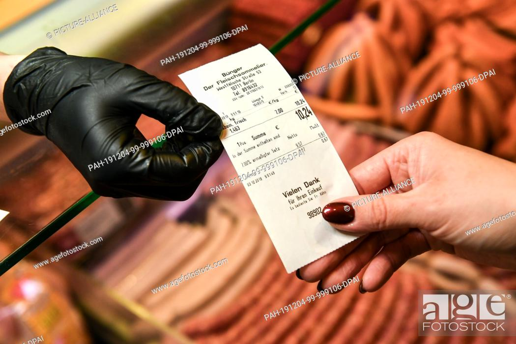 Stock Photo: 03 December 2019, Berlin: A butcher's shop assistant gives the receipt to a customer. Photo: Jens Kalaene/dpa-Zentralbild/ZB - ATTENTION: Only for editorial use.