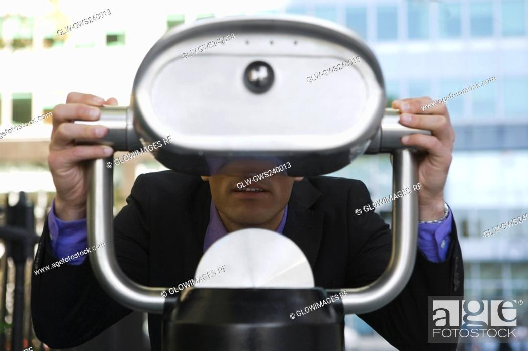 Stock Photo: Businessman looking through a coin-operated binoculars.