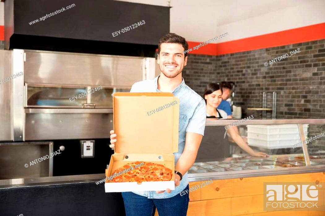 Stock Photo: Smiling customer with box showing pizza standing at pizza counter in pizzeria.