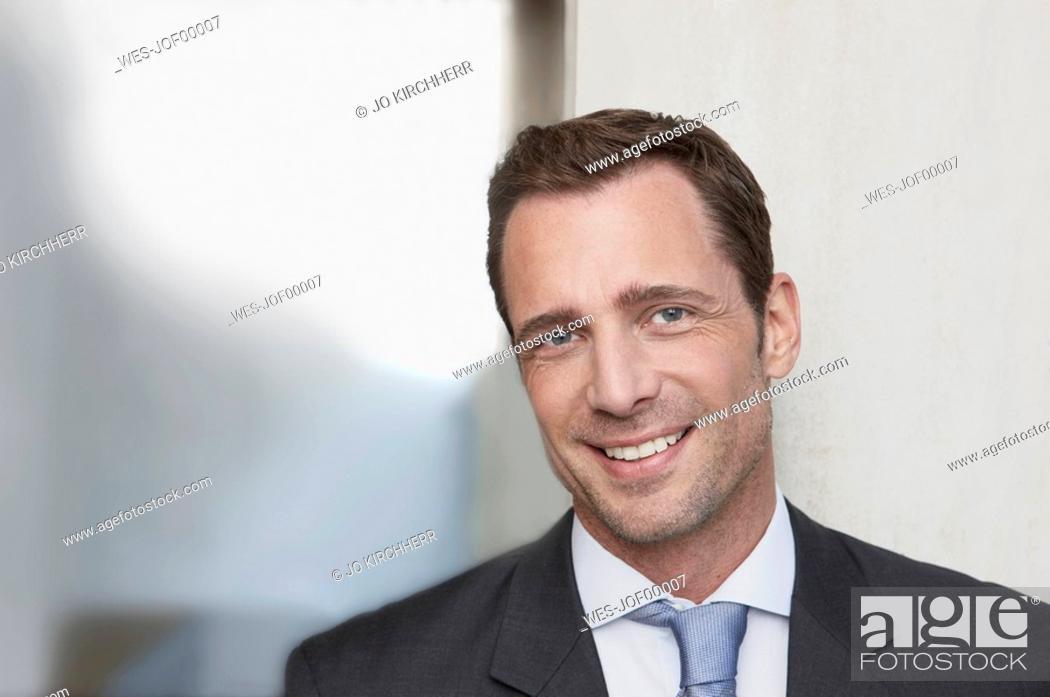 Stock Photo: Germany, Cologne, Businessman smiling, portrait, close-up.