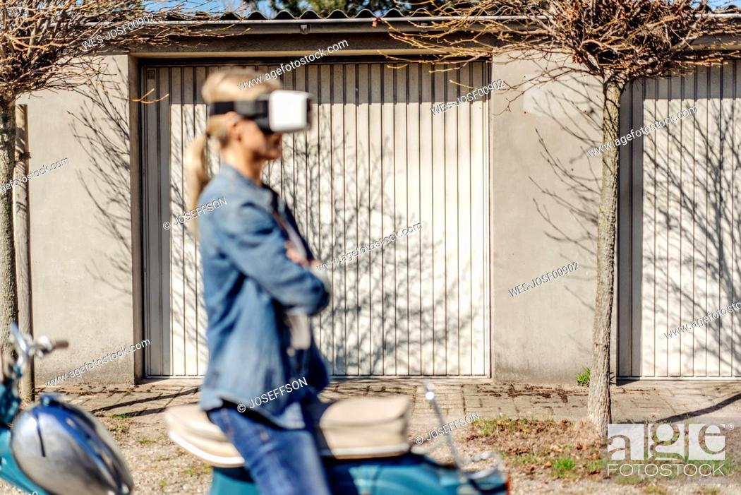 Stock Photo: Woman sitting backwards on vintage motorcycle wearing VR glasses.