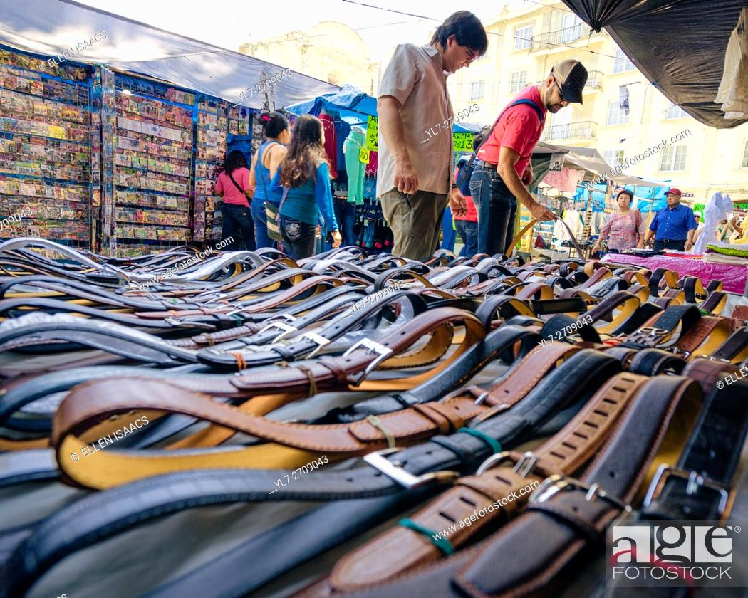 Stock Photo: Men shopping for leather belts at the Zocalo market in Oaxaca Mexico.