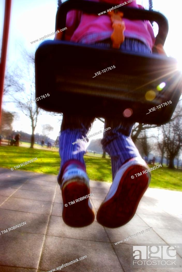 Stock Photo: Rearview legs and torso 6 year girl sitting on swing in childrens playground.