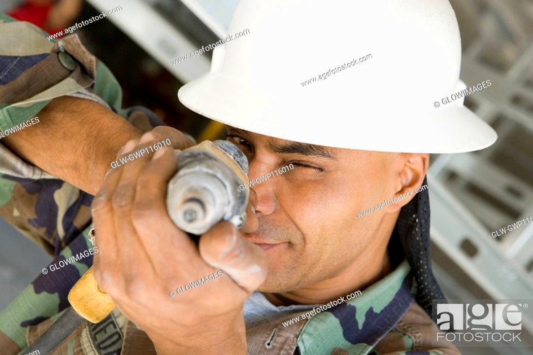 Stock Photo: Close-up of a male construction worker aiming with a hand drill.