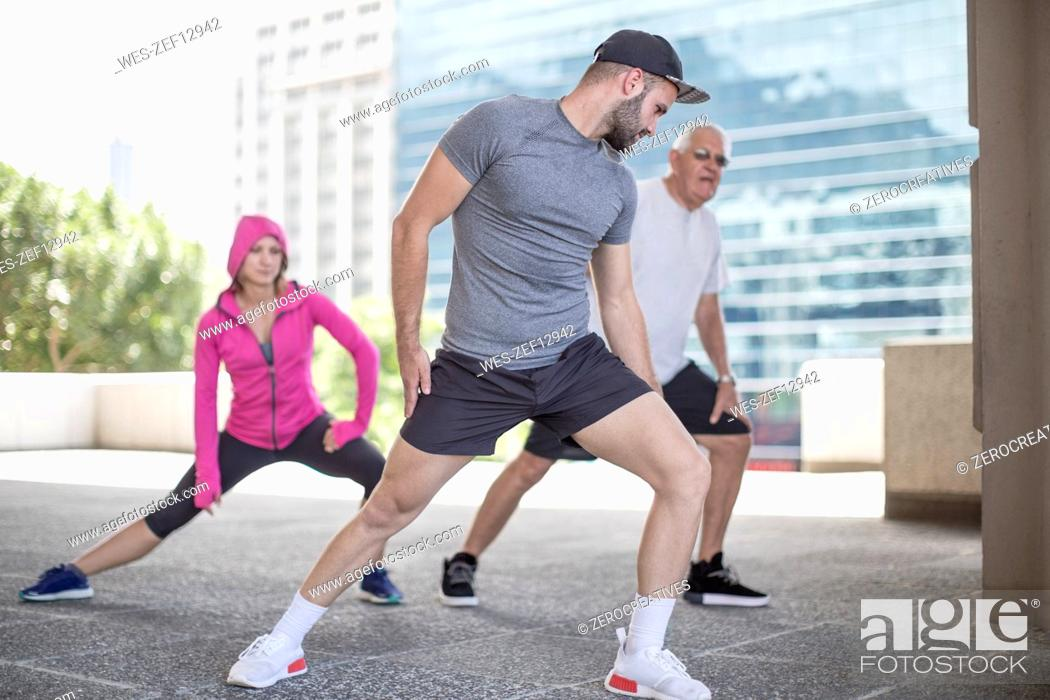 Stock Photo: Three athletes stretching in the city.