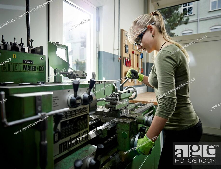 Stock Photo: Young woman working on lathe, Metalwork, training.