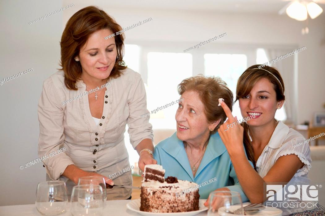 Stock Photo: A woman serving cake for her mother and daughter.