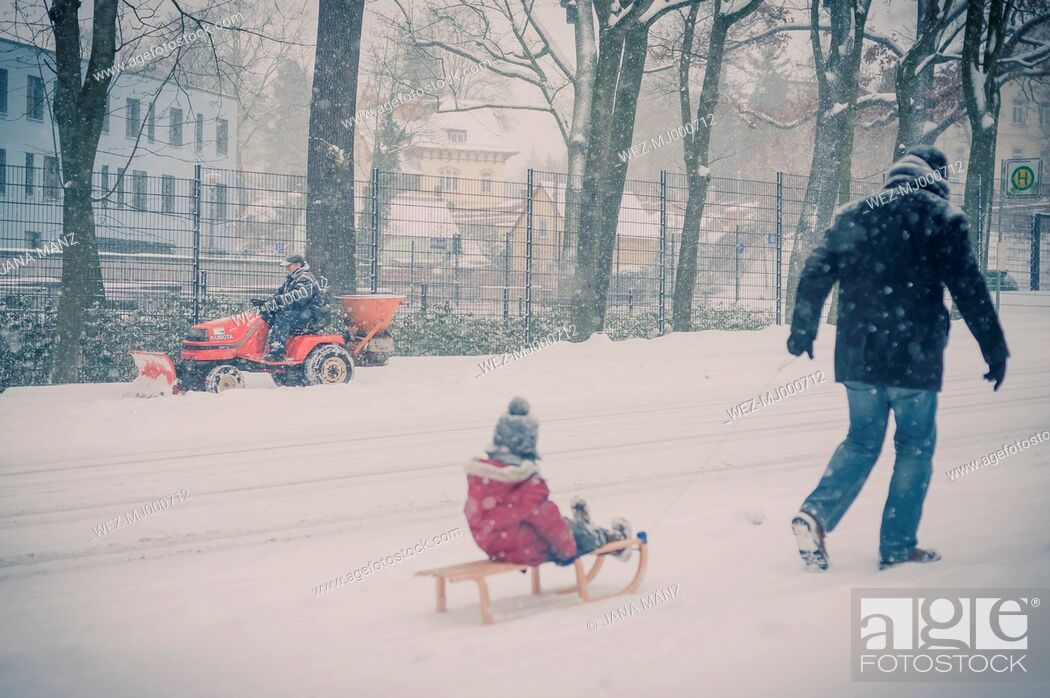 Stock Photo: Father pulling sledge with son in snow.