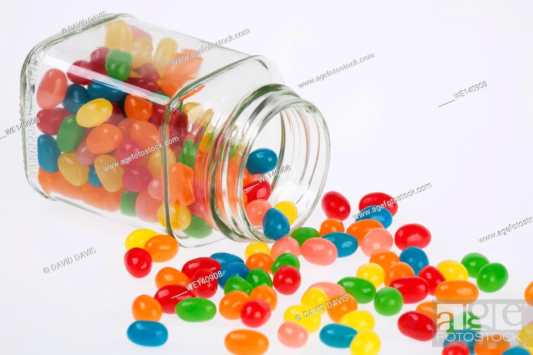 Stock Photo: Close up of a delicious Jelly Beans candy spilled from a glass jar isolated on a white background.
