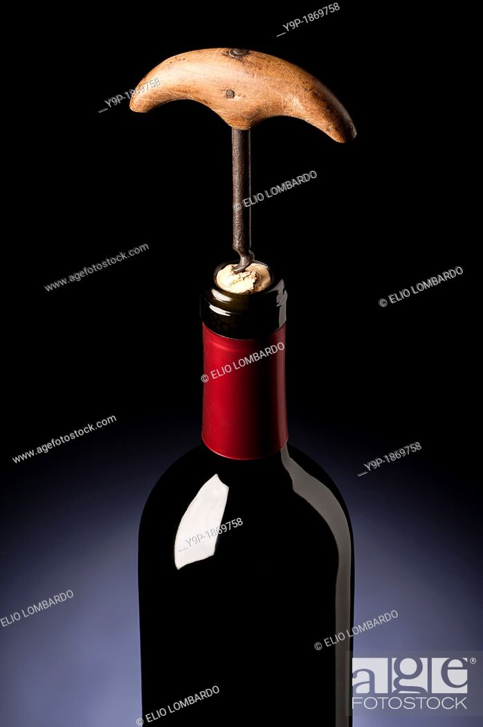 Stock Photo: Old Corkscrew Opening a Bottle of Wine.
