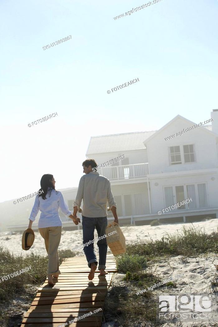 Stock Photo: Couple walking towards house on beach.