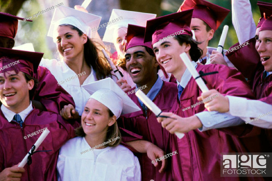 Stock Photo: Group of teenagers holding their degrees on graduation day.