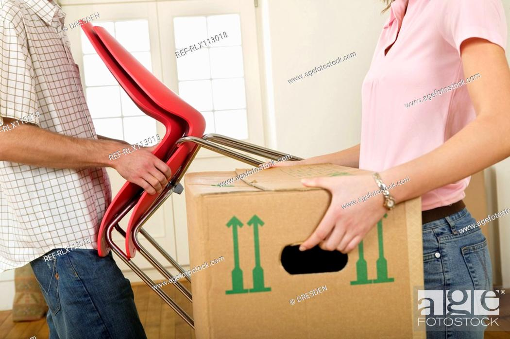 Stock Photo: Young couple carrying furniture.