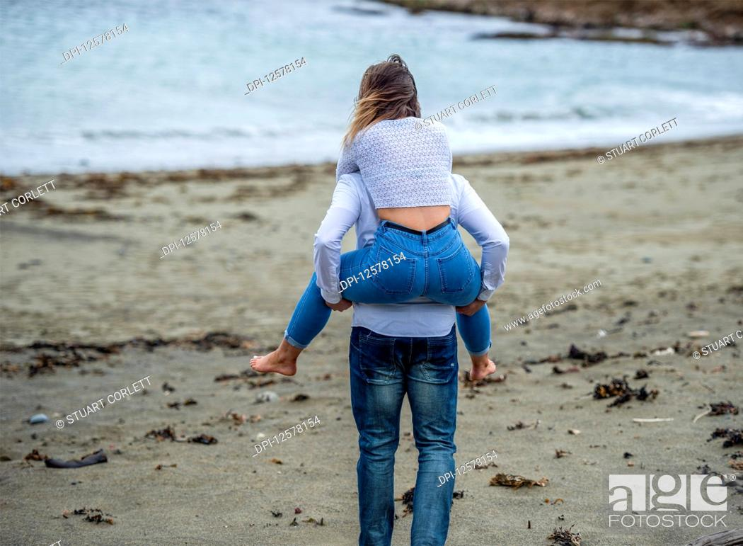 Stock Photo: A young couple at the beach, the young woman being carried on the young man's back; Wellington, North Island, New Zealand.