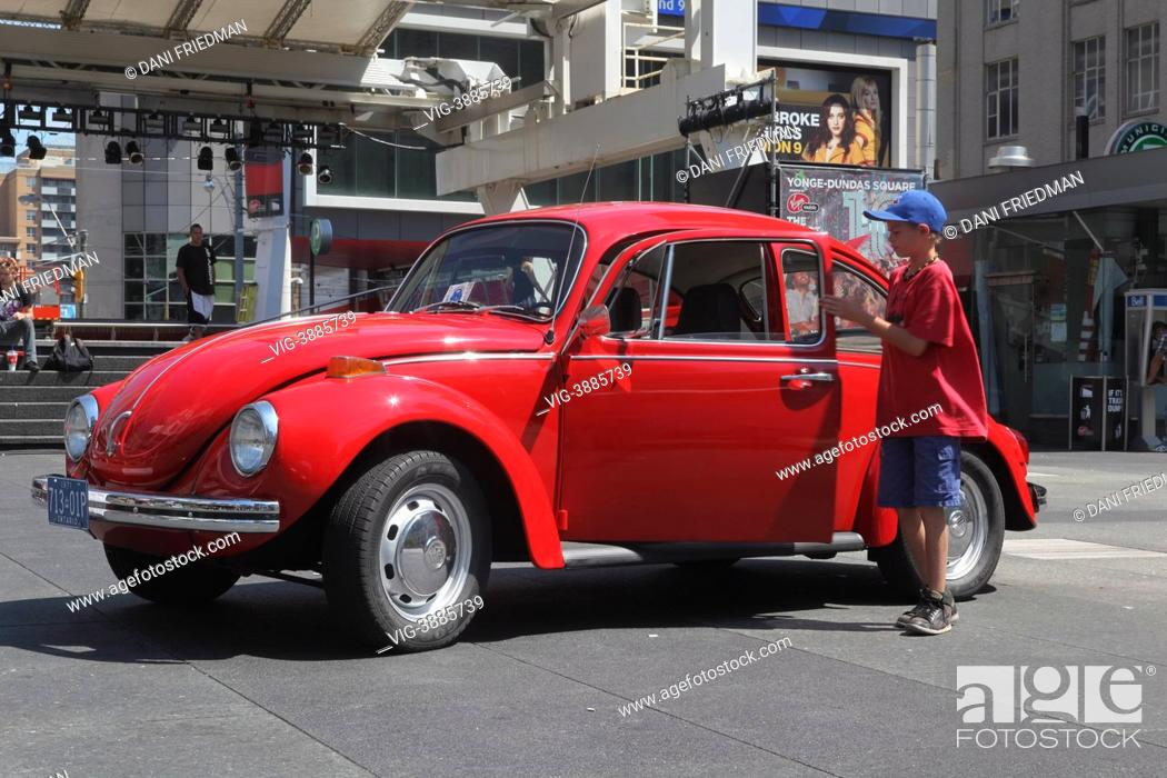 A boy examines a 1971 Volkswagen Beetle on display during a car show ...