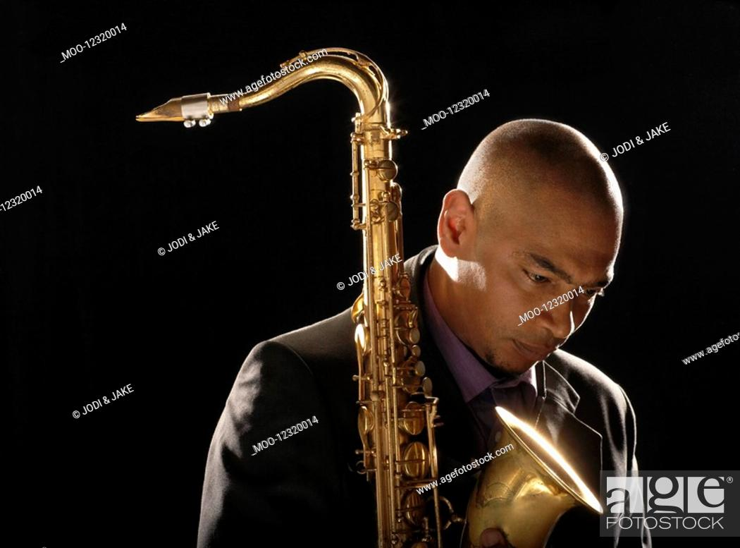 Stock Photo: Pensive man holding saxophone looking down close-up.