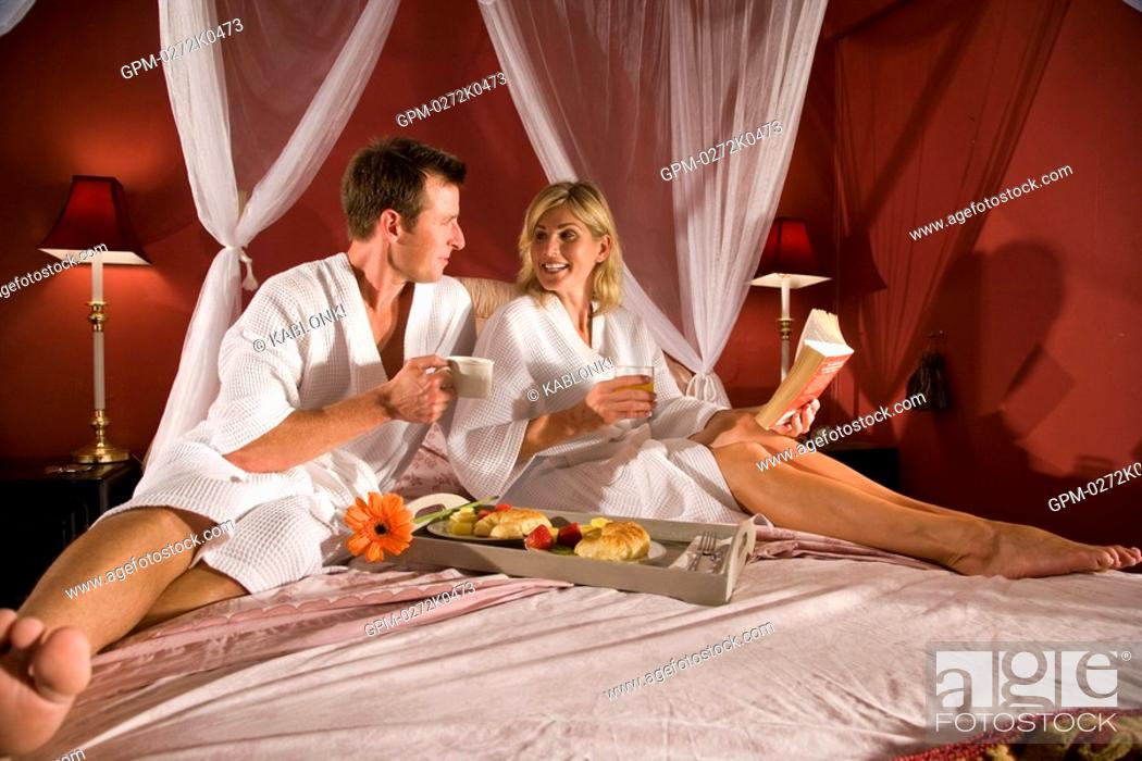 Stock Photo: Couple having breakfast in canopy bed.