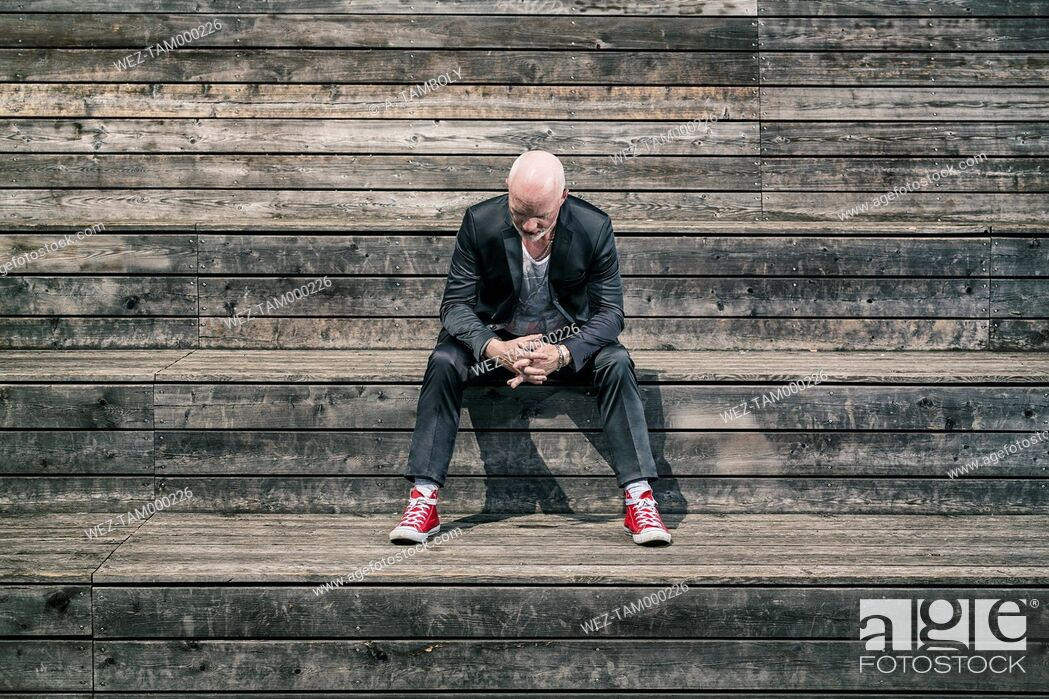 Stock Photo: Businessman weraing suit and red sneakers sitting on wooden stairs.