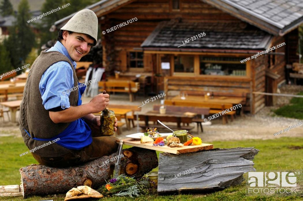 Stock Photo: Laughing man sitting in front of an alpine hut, Gostner Schwaige, Alpe di Siusi, South Tyrol, Italy, Europe.