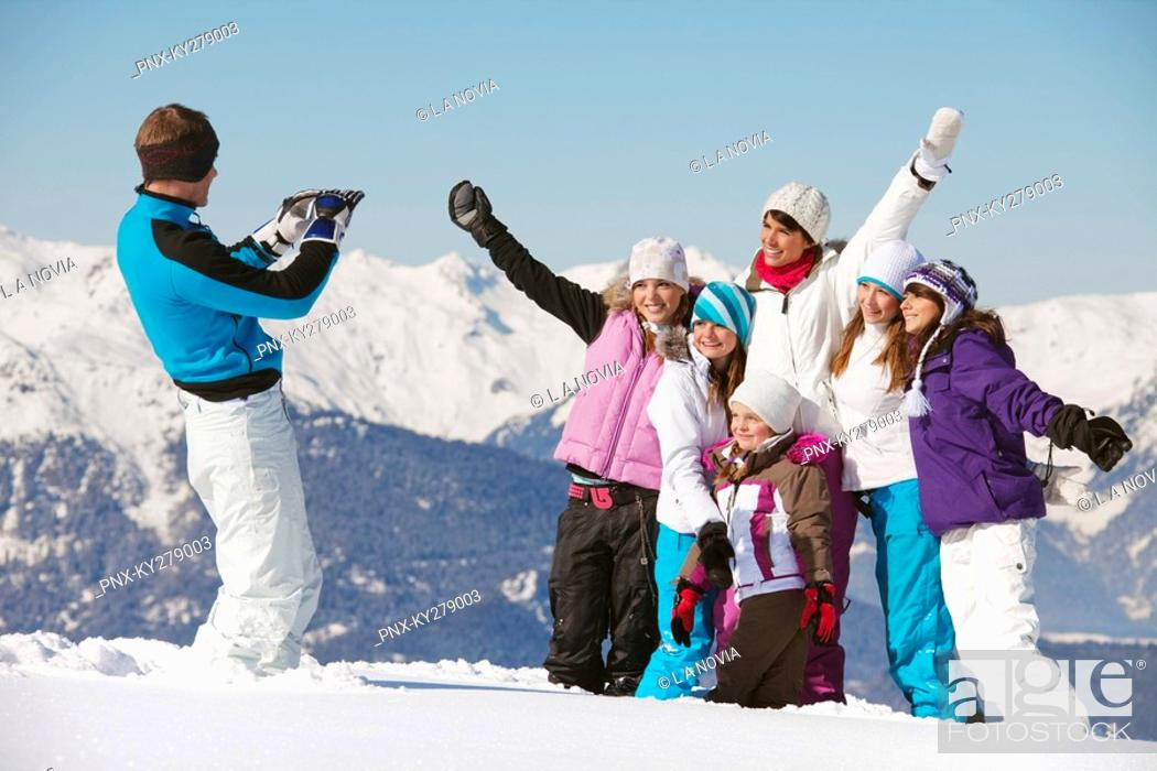 Stock Photo: Man taking picture of family in snow.