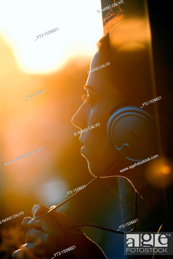Stock Photo: Young attractive girl using headphones, listening to her music at sunset.
