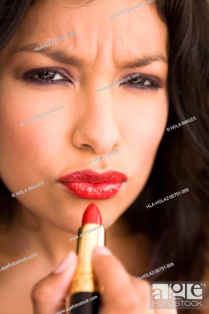 Imagen: Portrait of young woman putting on red lipstick.