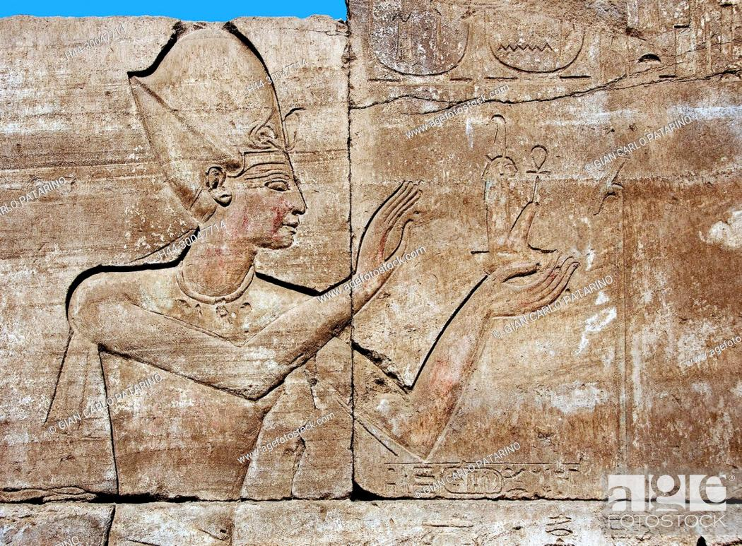 Stock Photo: Karnak, Luxor, Egypt. Temple of Karnak sacred to god Amon: sculpture in a wall showing a pharaoh with a little statue of the goddess Maat.