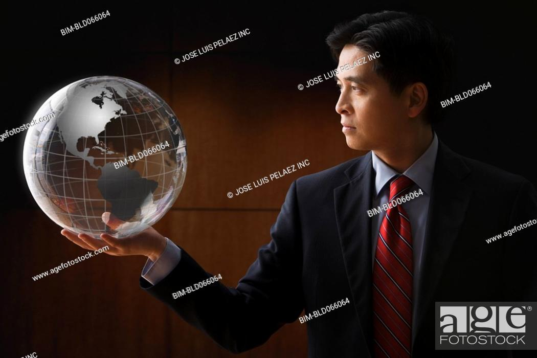 Stock Photo: Chinese businessman holding glass globe.
