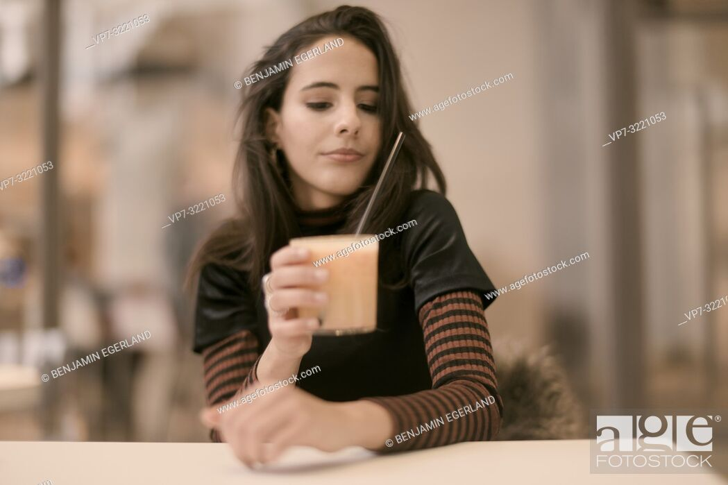Stock Photo: portrait of sensitive woman holding healthy juice glass while enjoying break at table in café, in Munich, Germany.