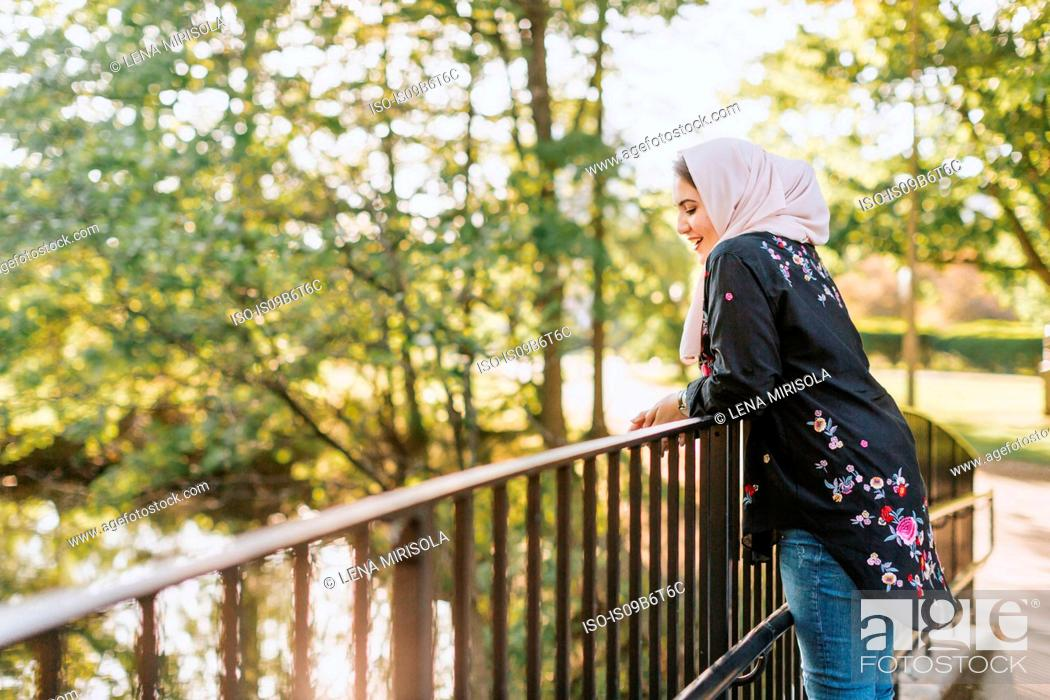 Stock Photo: Young woman wearing hijab on bridge looking away at view.