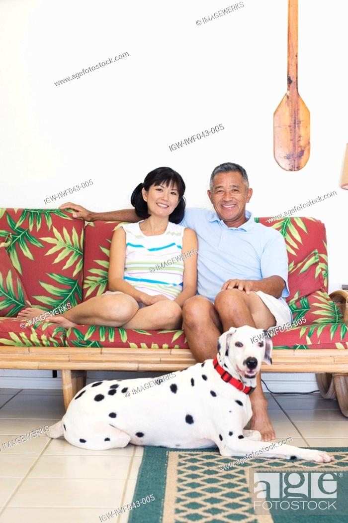 Stock Photo: A couple sitting on sofa with dog.