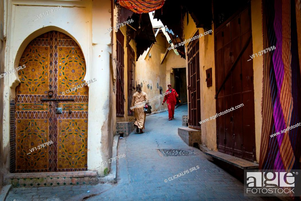 Stock Photo: Fes, Morocco, North Africa. Passers in the narrow streets of the medina.