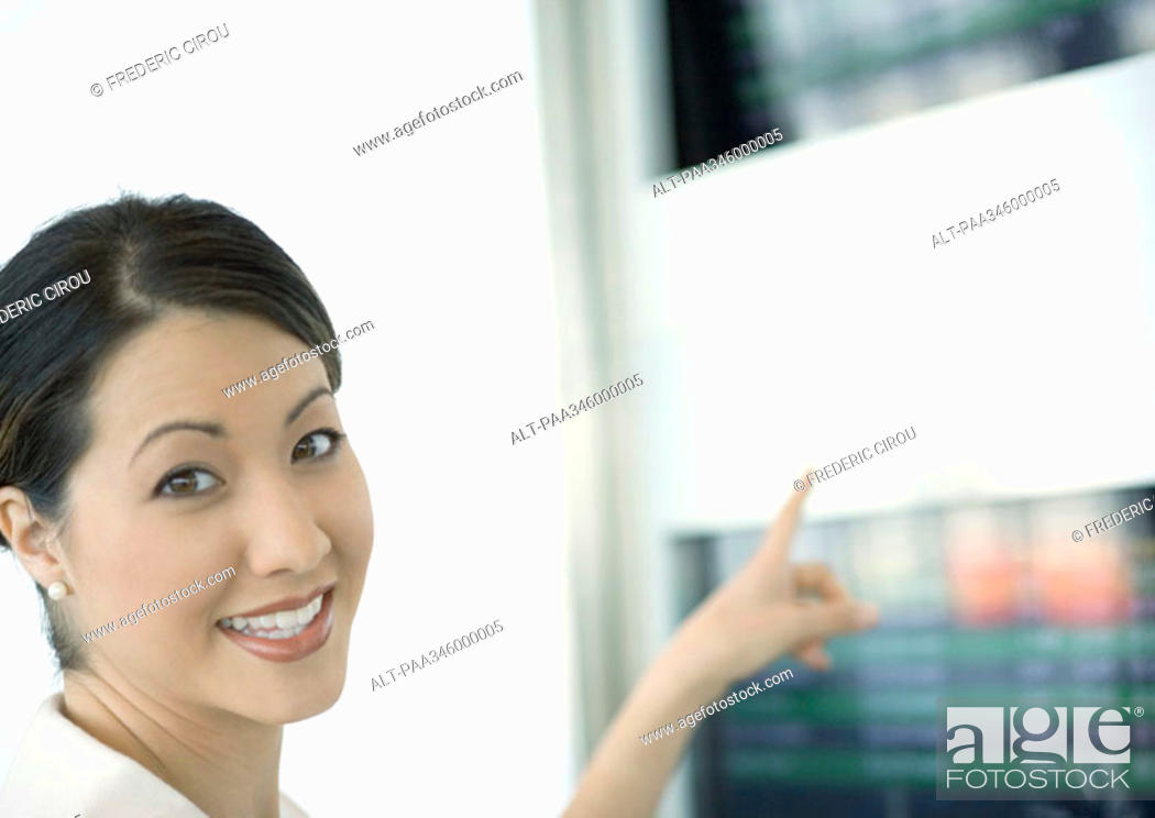 Stock Photo: Woman pointing to departure board.