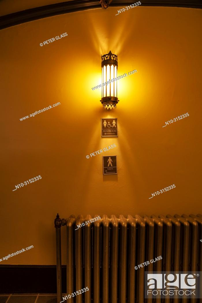 "Stock Photo: Light fixture on a wall with old cast iron radiator and signs reading """" Restroom"""" and """"Men"""" below it."