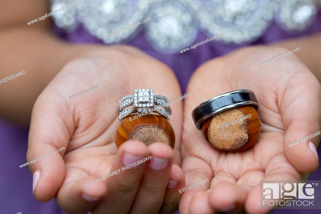 Stock Photo: Flower girl ring bearer holding wedding rings on filbert nuts at an outdoor orchard wedding in Oregon.